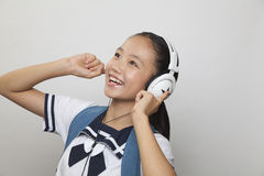 Girl in school uniform smiling and listening to music, Studio shot Royalty Free Stock Image