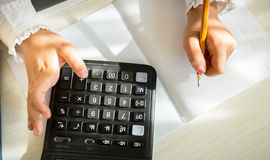 Girl in school uniform solving task with help of calculator Royalty Free Stock Photo