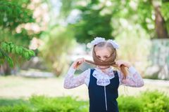 A  girl in school uniform spread her arms and rejoices at the completion of school. schoolgirl rejoices at the start of scho royalty free stock photo