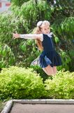 A  girl in school uniform spread her arms and rejoices at the completion of school. schoolgirl rejoices at the start of scho royalty free stock image