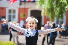 A  girl in school uniform spread her arms and rejoices at the completion of school. schoolgirl rejoices at the start of scho royalty free stock photography