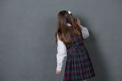 Girl in school uniform standing at the chalkboard. Girl in school uniform standing at the blackboard and writes that Royalty Free Stock Image