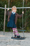 Girl in school uniform on a swing. Happy pupil in british school uniform standing on a swing royalty free stock photography