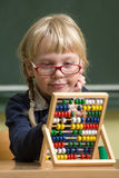 Girl in school working with abacus Stock Photo