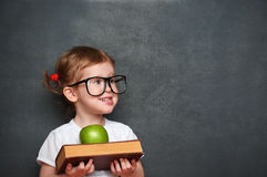 Girl schoolgirl with books and apple in a school board Royalty Free Stock Images