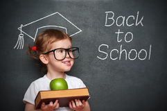 Girl schoolgirl with books and apple in a school board Royalty Free Stock Image