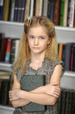 Girl schoolgirl in the library Royalty Free Stock Photos