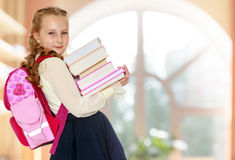 Girl schoolgirl with a satchel behind shoulders and books in han Royalty Free Stock Photo
