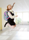 Girl schoolgirl with a satchel behind shoulders jumps. Happy girl schoolgirl in black dress and white shirt and a knapsack on his shoulders. She jumps, hands up Royalty Free Stock Photography