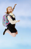 Girl schoolgirl with a satchel behind shoulders jumps. Happy girl schoolgirl in black dress and white shirt and a knapsack on his shoulders. She jumps, hands up Stock Photos