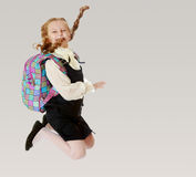 Girl schoolgirl with a satchel behind shoulders jumps. Happy girl schoolgirl in black dress and white shirt and a knapsack on his shoulders. She jumps, hands up Royalty Free Stock Photo