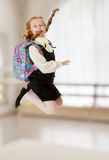 Girl schoolgirl with a satchel behind shoulders jumps. Happy girl schoolgirl in black dress and white shirt and a knapsack on his shoulders. She jumps, hands up Stock Photography