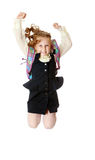 Girl schoolgirl with a satchel behind shoulders jumps. Joyful girl schoolgirl in black dress and white shirt and a knapsack on his shoulders. She jumps, hands up Royalty Free Stock Images