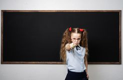 Girl schoolgirl at the school board shows a pointer forward. royalty free stock image