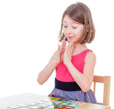 Girl schoolgirl sits at a table and lay cards. Royalty Free Stock Images