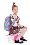 Girl schoolgirl sitting on a stack of books behind Royalty Free Stock Images