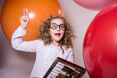 Girl schoolgirl with a surprised look with wooden abacus. Royalty Free Stock Image