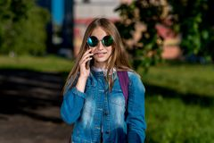 Girl schoolgirl teenager. In the summer in city. In his hands holds a smartphone. In jeans clothes, sunglasses. He talks. Girl schoolgirl teenager. In the summer stock images