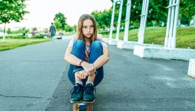 Girl schoolgirl 12-15 years old, sitting in the summer in the city on a skateboard, asphalt road. Sad tired, rest after royalty free stock images