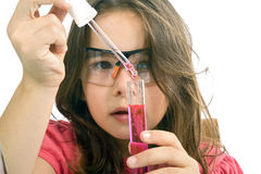 Girl in science class. Young girl examining a test tube in a science class