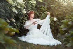 Girl with scissors makes the wedding dress. Among the flowering shrubs girl with scissors makes a wedding dress stock image