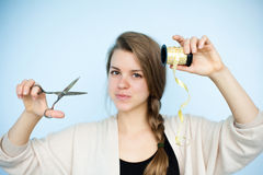 Girl with scissors and packing tape. Woman preparing to decorate a gift Stock Photography