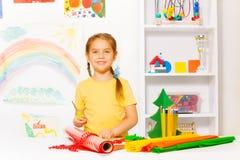 Girl with scissors standing near white desk Stock Photo