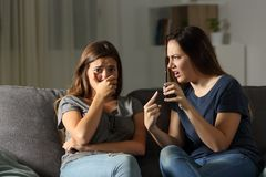 Girl scolding her sad friend about media content. Sitting on a couch in the living room at home Royalty Free Stock Images