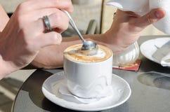 Girl scoop a teaspoon of coffee foam Royalty Free Stock Images