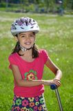 Girl with a Scooter. Girl plays safe and wears a helmet when she rides her scooter Royalty Free Stock Image