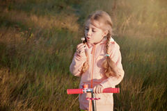 Girl with scooter blowing on a dandelion Royalty Free Stock Photo