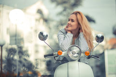 Girl on a scooter. In the city Stock Images