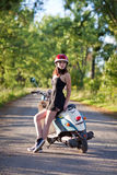 A girl with a scooter on a country road Royalty Free Stock Images