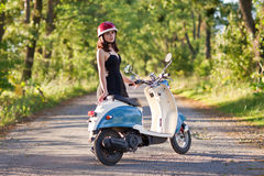 A girl with a scooter on a country road Stock Image