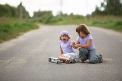 Girl  scooter fell  In the countryside,  sister helps her child Royalty Free Stock Images