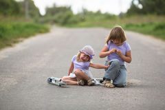 Girl  scooter fell  In the countryside,  sister helps her child Stock Photos