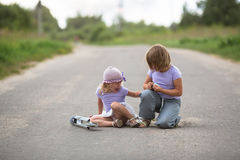 Girl  scooter fell  In the countryside,  sister helps her child Royalty Free Stock Photos