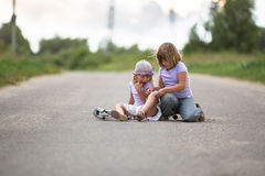 Girl  scooter fell  In the countryside,  sister helps her child Royalty Free Stock Photography