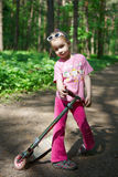 Girl with a scooter in the park Stock Photography