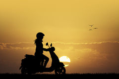 Girl on scooter at sunset Stock Images