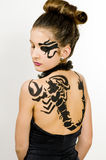Girl with scorpio painted on back. Girl with black scorpio sign painted on back and face stock photography