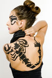 Girl with scorpio painted on back. Girl with black scorpio sign painted on back and face stock image