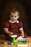 Girl in the scottish dress. Plays with the cubes Stock Photography