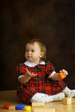 Girl in the scottish dress. Plays with the cubes Royalty Free Stock Image