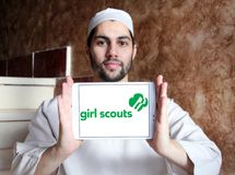 Girl Scouts of the USA logo. Logo of Girl Scouts of the USA on samsung tablet holded by arab muslim man. Girl Scouts, is a youth organization for girls in the stock photos
