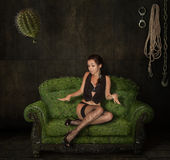 A girl on a scratchy sofa Stock Images