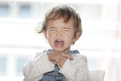 Girl screaming. Portrait of little girl  sitting and screaming Royalty Free Stock Photography