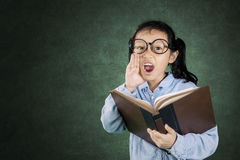 Girl screaming with book in her hand Stock Photo