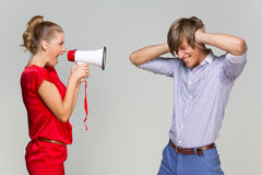 Girl screaming at boyfriend. Young women screaming at her boyfriend with mehaphone over grey background Royalty Free Stock Photos