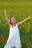 Girl screaming with delight. Pretty young girl screaming with delight surrounded by rapeseed flowers and poppies Royalty Free Stock Image